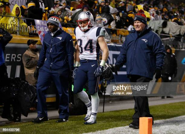 Rex Burkhead of the New England Patriots walks off the field with trainers in the third quarter during the game against the Pittsburgh Steelers at...