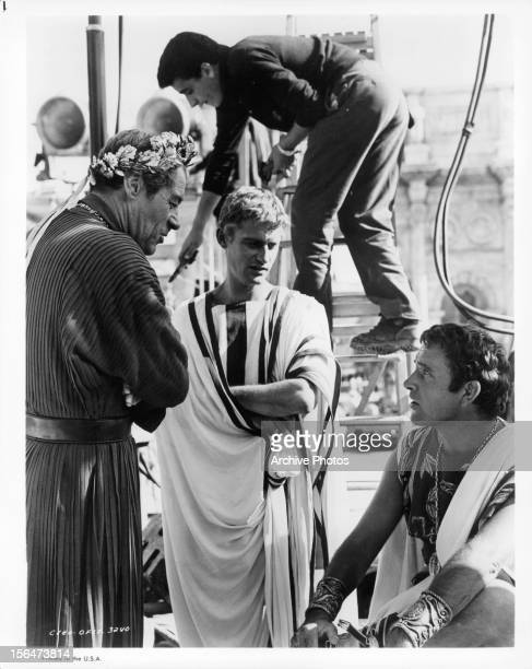 Rex Harrison and Roddy McDowall looking down at Richard Burton on the set of the film 'Cleopatra' 1963