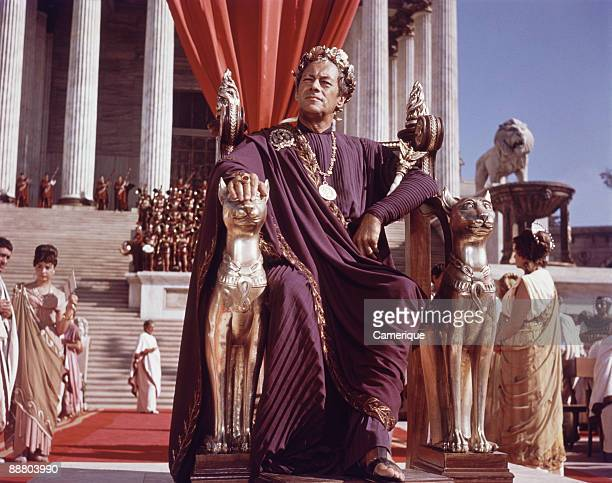 Rex Harrison playing Julius Caesar sits on an ornately decorated throne from the movie Cleopatra 1963
