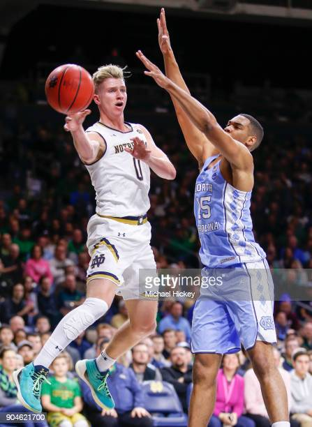Rex Pflueger of the Notre Dame Fighting Irish passes the ball off as Garrison Brooks of the North Carolina Tar Heels defends at Purcell Pavilion on...
