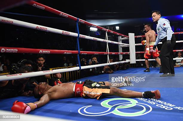 Rey Juntilla of the Philippines walks to his corner after knocking down Defry Palulu of Indonesia during a curtainraiser match during a WBO Asia...