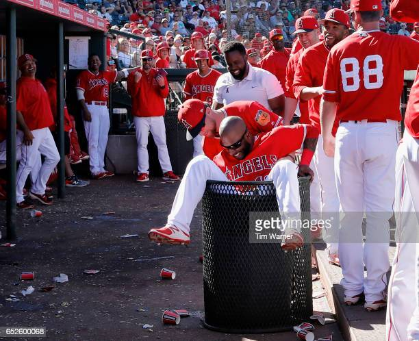 Rey Navarro of the Los Angeles Angels of Anaheim falls into a trash can after a line drive went into the Angels' dugout in the eighth inning during a...