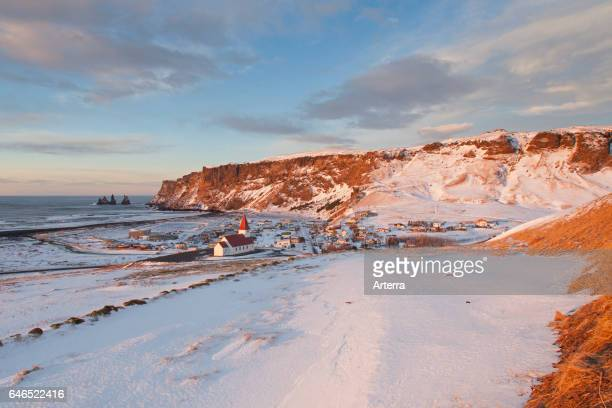 Reynisdrangar sea stacks and the Vik church at the village Vik i Myrdal in winter Iceland