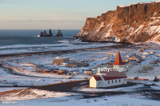 Reynisdrangar sea stacks and the Vik church at the village Vik i Myrdal in winter Iceland