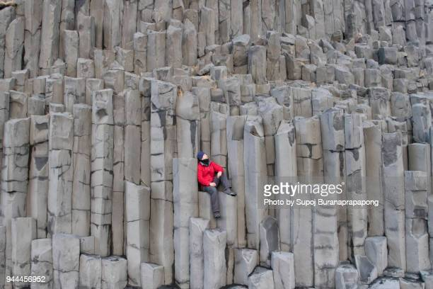 reynisfjall mountain cliff basalt column at reynisfjara black sand beach in south coast,iceland.a man in red jacket sitting on basalt column cliff  looking at beautiful landscape inspiration and motivation concept. - basalt stock pictures, royalty-free photos & images