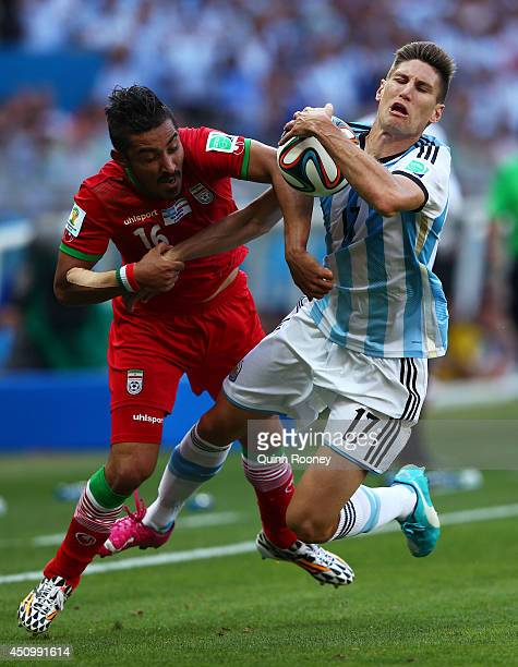 Reza Ghoochannejhad of Iran and Federico Fernandez of Argentina compete for the ball during the 2014 FIFA World Cup Brazil Group F match between...