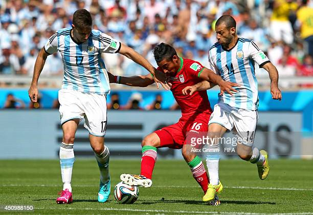 Reza Ghoochannejhad of Iran competes for the ball against Federico Fernandez and Javier Mascherano of Argentina during the 2014 FIFA World Cup Brazil...