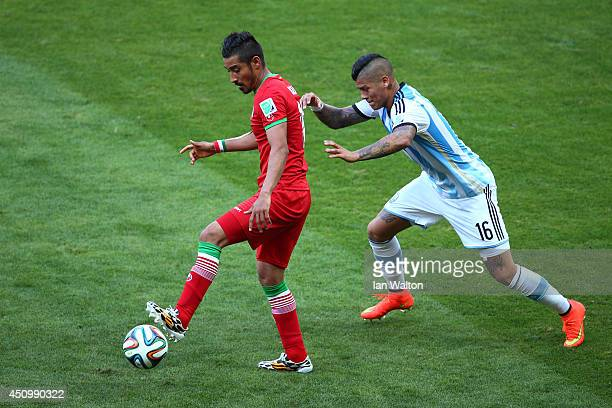 Reza Ghoochannejhad of Iran controls the ball as Marcos Rojo of Argentina gives chase during the 2014 FIFA World Cup Brazil Group F match between...