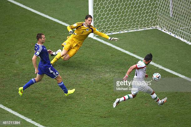 Reza Ghoochannejhad of Iran shoots and scores his team's first goal past goalkeeper Asmir Begovic of Bosnia and Herzegovina during the 2014 FIFA...