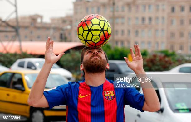 Reza Parastesh a doppelganger of Barcelona and Argentina's footballer Lionel Messi juggles a ball in a street in Tehran on May 8 2017 / AFP PHOTO /...