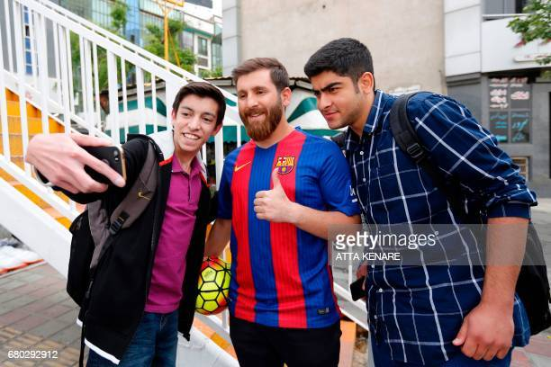 Reza Parastesh a doppelganger of Barcelona and Argentina's footballer Lionel Messi poses for a picture with fans in a street in Tehran on May 8 2017...