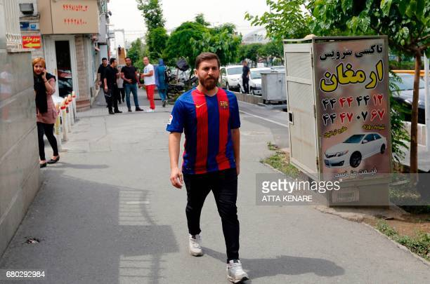 Reza Parastesh a doppelganger of Barcelona and Argentina's footballer Lionel Messi walks down a street in Tehran on May 8 2017 / AFP PHOTO / ATTA...