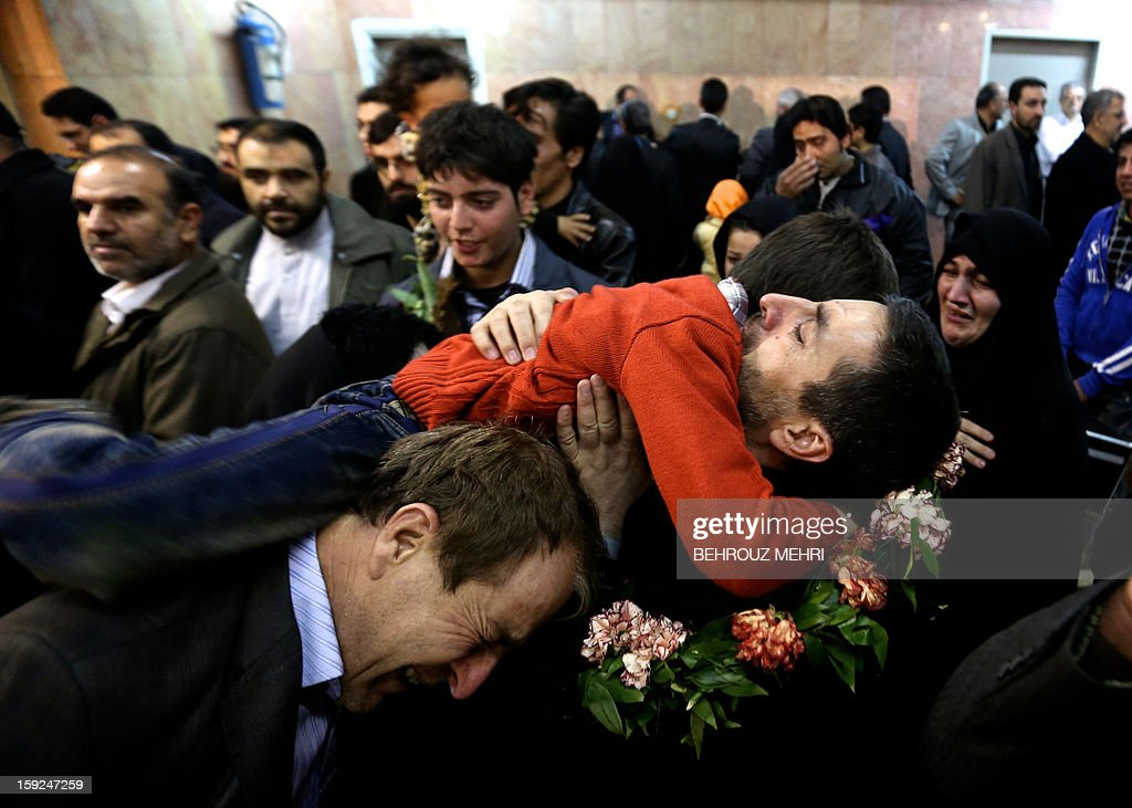 Reza Sohrabi, an Iranian man who has been held hostage, alongside 48 other Iranians, by Syrian rebels since early August 2012, hugs his son after arriving at Tehran's Mehrabad airport on January 10, 2013. The rebels agreed to swap the 48 Iranians, described by the Islamic republic as pilgrims but by the rebels and Washington as members of Iran's elite Revolutionary Guards, for more than 2,000 detainees held by the Syrian regime.