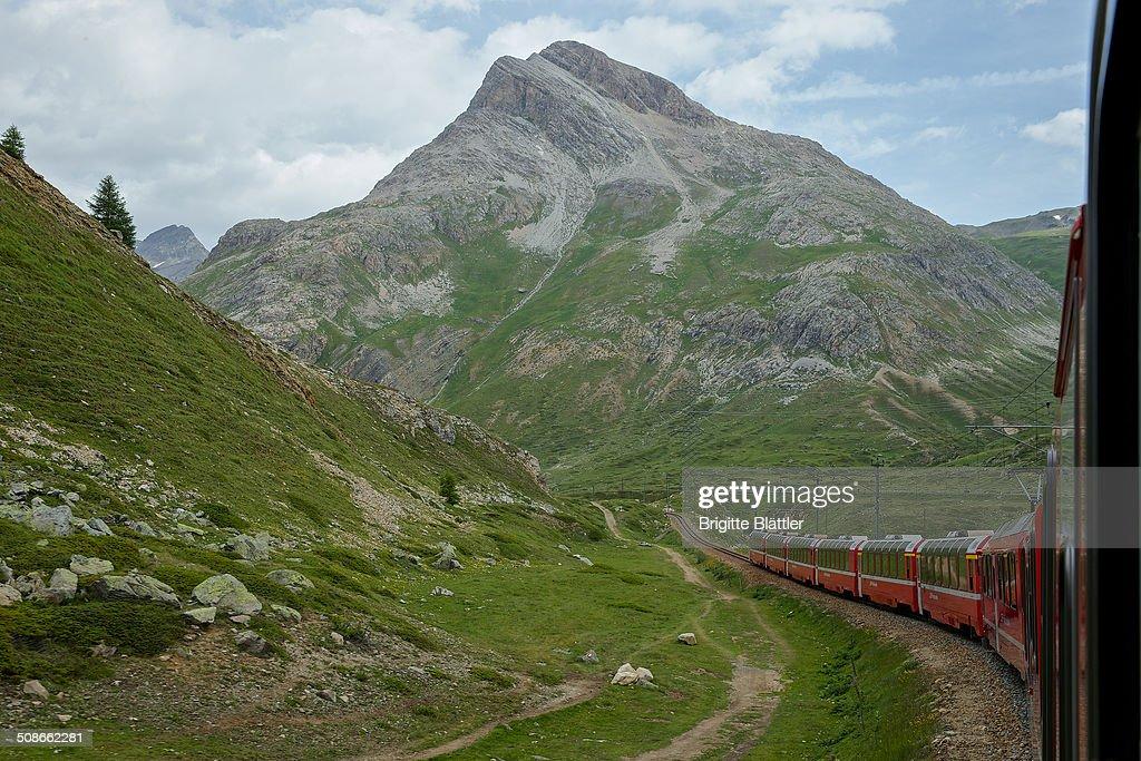 RHB, Rhaetian Railway, Rhätische Bahn, winds through mountain landscape in Grisons, Engadin, Switzerland.