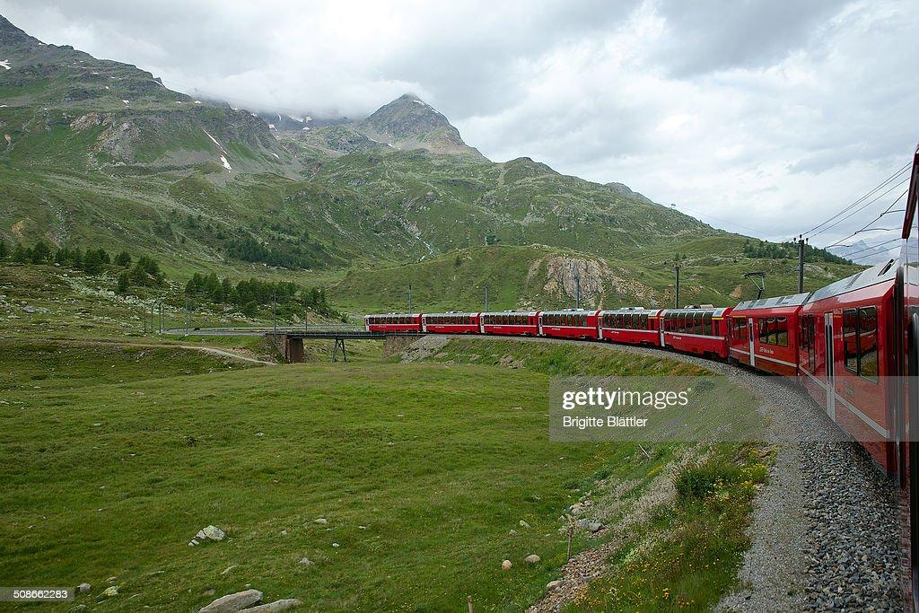 RHB, Rhaetian Railway, Rhätische Bahn, winds through mountain landscape in Engadin, Switzerland.