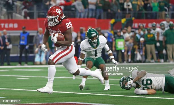 Rhamondre Stevenson of the Oklahoma Sooners runs the ball across the goal line to score the winning touchdown in overtime of the Big 12 Football...