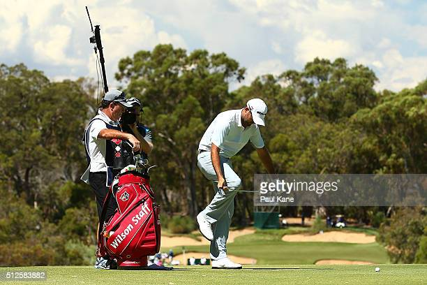 Rhein Gibson of Australia bends his iron back into shape after playing his second shot from the rough on the 6th hole during day three of the 2016...