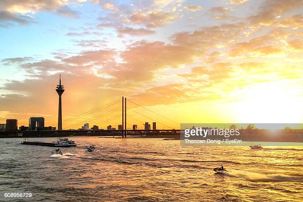 Rheinturm Tower In Front Of River Against Cloudy Sky During Sunset In City
