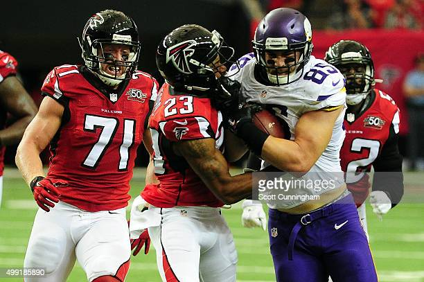 Rhett Ellison of the Minnesota Vikings is tackled by Robert Alford and Kroy Biermann of the Atlanta Falcons during the first half at the Georgia Dome...