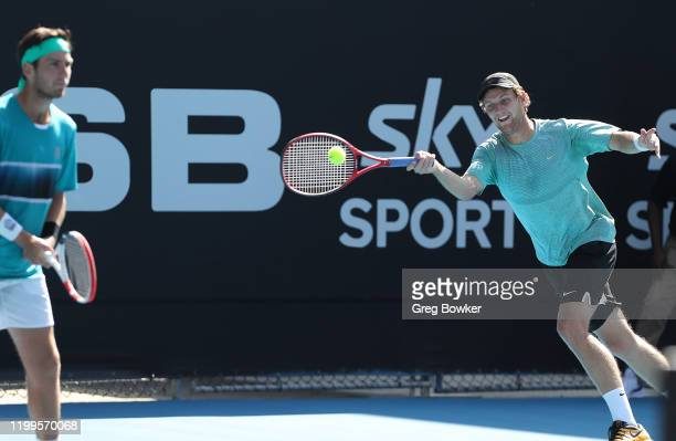 Rhett Purcell of New Zealand plays a forehand with his doubles partner Cameron Norrie of Great Britain in action against Rohan Bopanna of India and...