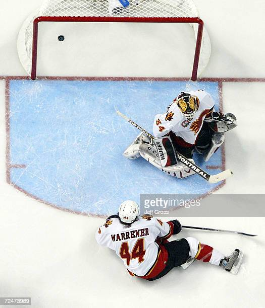Rhett Warrener and goaltender Miikka Kiprusoff of the Calgary Flames watch as a shot by Brad Richards of the Tampa Bay Lightning scores during the...