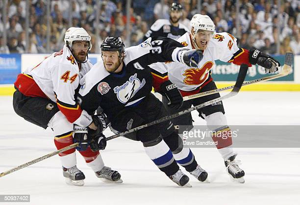 Rhett Warrener and Ville Nieminen of the Calgary Flames defend Fredrik Modin of the Tampa Bay Lightning in game seven of the NHL Stanley Cup Finals...