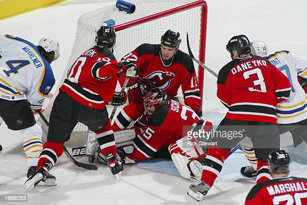Rhett Warrener of the Buffalo Sabres tries to force the puck past goaltender Corey Schwab of the New Jersey Devils as Oleg Tverdovsky Jeff Friesen...