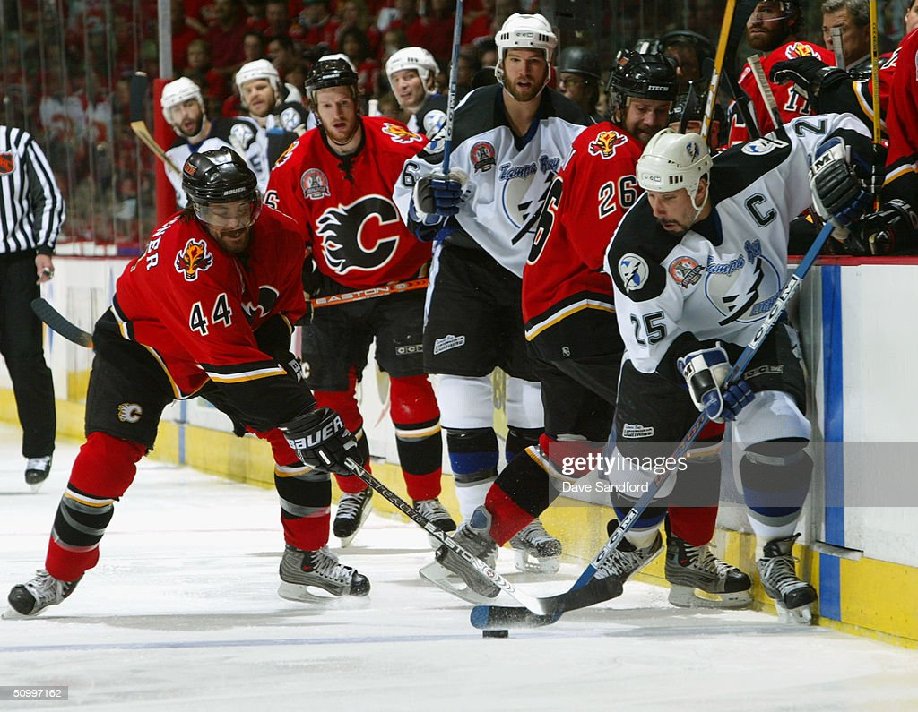 Rhett Warrener #44 of the Calgary Flames goes for the stick check against Dave Andreychuk #25 of the Tampa Bay Lightning in Game four of the NHL Stanley Cup Finals on May 31, 2004 at the Pengrowth Saddledome in Calgary, Canada. The Lightning defeated the Flames 1-0.