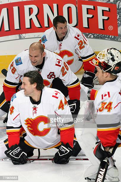Rhett Warrener Robyn Regehr Craig Conroy and Miikka Kiprusoff of the Calgary Flames share a laugh during warm up before their game against the...
