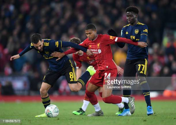 Rhian Brewster of Liverpool is held back by Dani Ceballos and Bukayo Saka of Arsenal during the Carabao Cup Round of 16 match between Liverpool and...