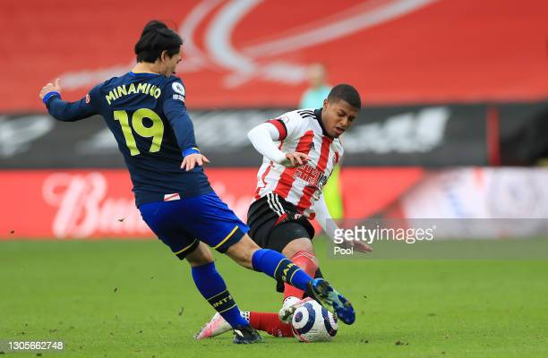 Rhian Brewster of Sheffield United is challenged by Takumi Minamino of Southampton during the Premier League match between Sheffield United and...