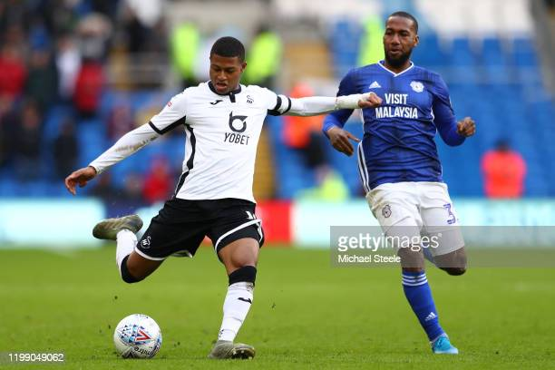 Rhian Brewster of Swansea City shoots as Junior Hoilett of Cardiff City looks on during the Sky Bet Championship match between Cardiff City and...