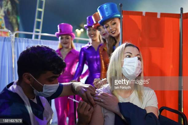 Rhiannon Alexander from Bradford receives a Covid 19 vaccination as circus performers look on during a staged photo at a new 'Pop Up' vaccination...