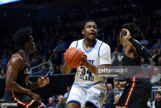 Rhode Island Rams forward Andre Berry defended by Charleston Cougars forward Osinachi Smart and Charleston Cougars forward Jaylen McManus during a...