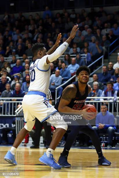 Rhode Island Rams forward Cyril Langevine and Duquesne Dukes center Jordan Robinson in action during a college basketball game between Duquesne Dukes...