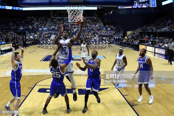 Rhode Island Rams forward Cyril Langevine drives to the basket defended by UNC Asheville Bulldogs guard MaCio Teague during a college basketball game...