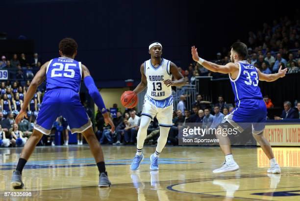 Rhode Island Rams guard Stanford Robinson defended by UNC Asheville Bulldogs guard MaCio Teague and UNC Asheville Bulldogs guard Drew Rackley during...