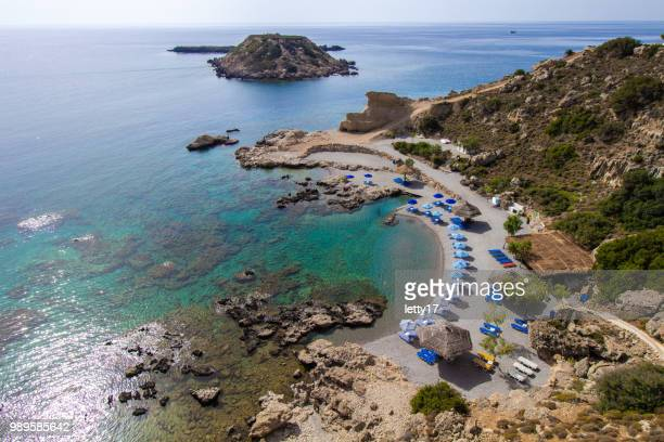 rhodes island, greece. aerial panorama of small beach with row of umbrellas and sun chairs. - lindos stock photos and pictures