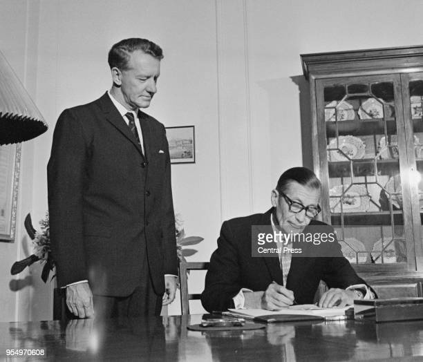 Rhodesian Prime Minister Ian Smith watches Clifford Dupont the Officer Administrating the Government of Rhodesia sign the new constitution bill in...