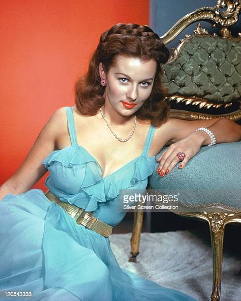 Rhonda Fleming US actress wearing a blue dress with a silver belt as she sits on the floor resting an arm on a chair beside her in a studio portrait...