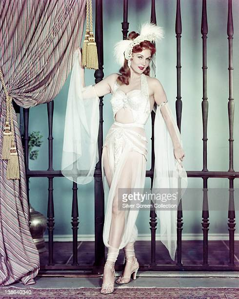 Rhonda Fleming US actress wearing a white sheer outfit with white feathers in her hair in a studio portrait circa 1955