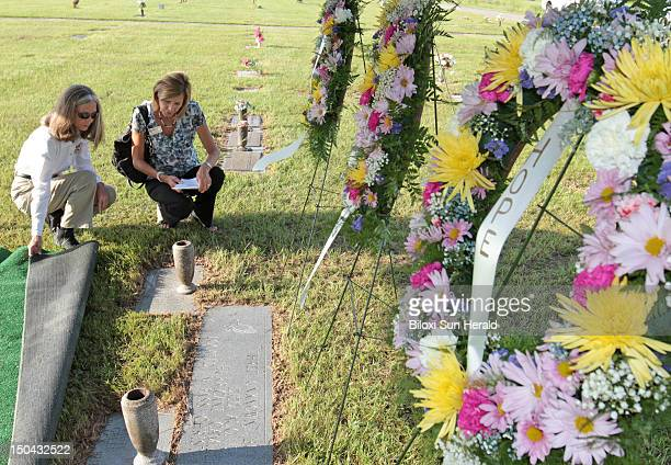 Rhonda Haynes of the Harrison County Emergency Management Office, left, and Kathleen Shaughnessy of AT&T look at the graves of Faith, Hope and...