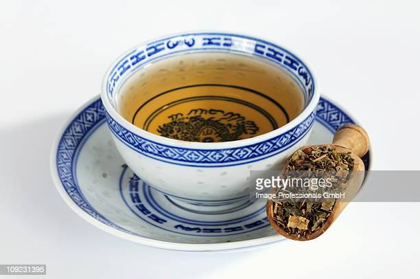 Rhubarb root in wooden scoop with tea cup