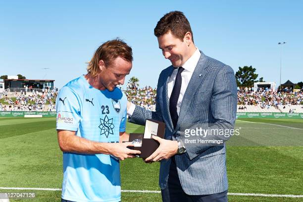 Rhyan Grant of Sydney is presented an award for becoming Sydney FC's first 10 year player during the round 17 ALeague match between Sydney FC and...