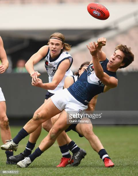Rhylee West of Vic Metro handballs whilst being tackled during the 2018 U18 Championships match between Vic Country and Vic Metro at Melbourne...
