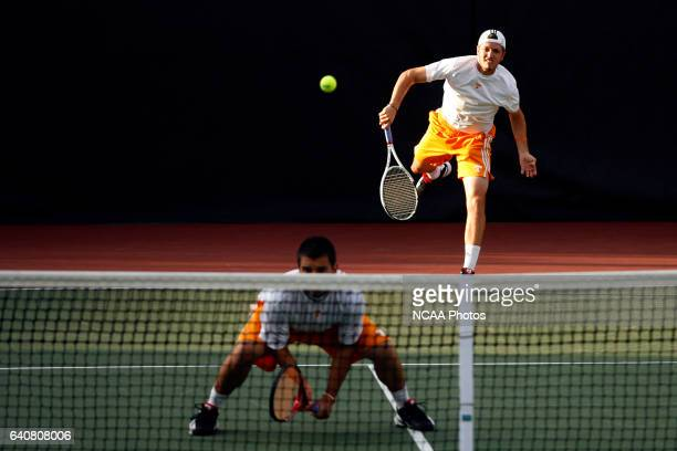 Rhyne Williams of the University of Tennessee serves against the University of Southern California in a doubles match during the Division I Men's...