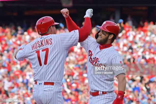 Rhys Hoskins and Bryce Harper of the Philadelphia Phillies celebrate Hoskins grand slam in the seventh inning against the Atlanta Braves on Opening...