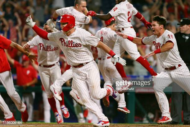 Rhys Hoskins and the rest of the Philadelphia Phillies celebrate after Bryce Harper hit a walk-off two run double in the ninth inning to defeat the...