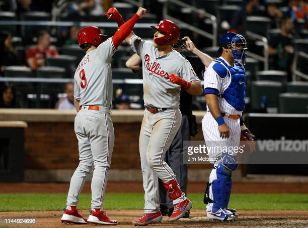 Rhys Hoskins of the Philadelphia Phillies celebrates his ninth inning two run home run with teammate Bryce Harper as Wilson Ramos of the New York...
