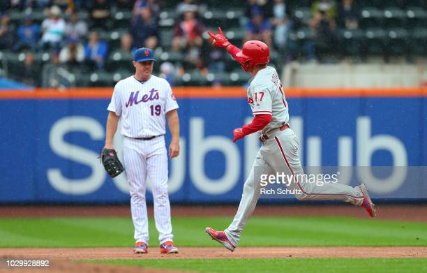 Rhys Hoskins of the Philadelphia Phillies gestures as he passes Jay Bruce of the New York Mets after he hit a tworun home run against the New York...